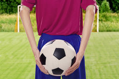 Soccer player holds ball at behind Stock Photos