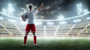Soccer player holds a soccer ball on the professional stadium and talking to fans. View from behind stock images