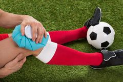 Soccer player icing knee with ice pack Royalty Free Stock Photography