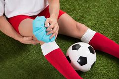 Soccer player icing knee with ice pack Stock Image