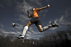 Soccer player jumping. Soccer player jump with ball Stock Photos