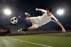 Soccer player jumping and kicking Stock Photography