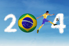 Soccer player kick the ball. A Brazilian soccer player kicking the ball on the clouds of 2014 stock photo