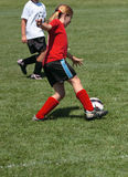 Soccer Player Kicking Ball. Girl soccer player kicking ball during game play Stock Photography