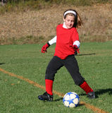 Soccer Player Kicking Ball 55. Girl soccer player kicking ball during game play Royalty Free Stock Image