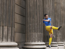 Soccer Player Kicking Ball Between Columns Royalty Free Stock Photography