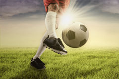 Soccer player kicking the ball at the green field Royalty Free Stock Photo