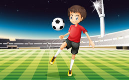 A soccer player kicking a ball Royalty Free Stock Image