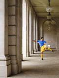 Soccer Player Kicking Ball In Portico Stock Photo