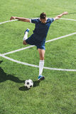 Soccer player kicking ball on soccer pitch Royalty Free Stock Photography