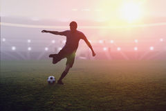 Soccer player is kicking a ball in stadium at sunset Royalty Free Stock Photos