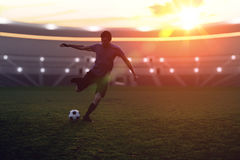 Soccer player is kicking a ball to the net in stadium at sunset Stock Images