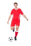 Soccer player kicking football Stock Photo