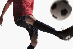 Soccer player kicking a soccer ball Royalty Free Stock Image