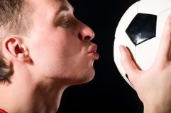 Soccer player is kissing the ball Royalty Free Stock Image