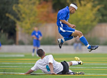 Soccer player Leaping over fallen athlete. October 15, 2008 Oregon High School Boys Varsity Soccer. Hillsboro's Hill Hi V Century High school. A Spartan leaps royalty free stock images