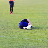 Soccer player lying down on football match Stock Photography