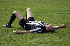 Soccer player lying down on grass Stock Image