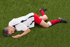 Soccer player lying on grass. Male Soccer Player Suffering From Injury Lying On Grass Stock Photo