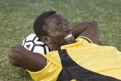 Soccer player lying with head on ball Stock Photography