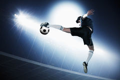 Soccer player in mid air kicking the soccer ball, stadium lights at night in background Stock Photography