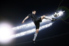 Soccer player in mid air kicking the soccer ball, stadium lights at night in background stock photos