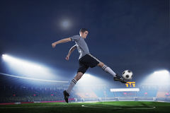 Soccer player in mid air kicking the soccer ball, stadium lights at night in background Royalty Free Stock Photography