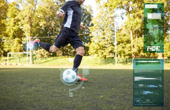Soccer player playing with ball on football field. Sport, technology and people concept - soccer player playing with ball on football field Royalty Free Stock Images