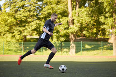 Soccer player playing with ball on football field Royalty Free Stock Images