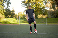 Soccer player playing with ball on football field Stock Photo