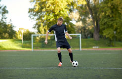 Soccer player playing with ball on football field Royalty Free Stock Image