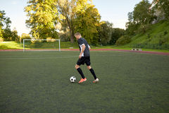 Soccer player playing with ball on football field Stock Photos