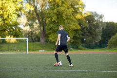 Soccer player playing with ball on football field Royalty Free Stock Photography