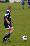 A soccer player playing football. Youth football player passing the ball royalty free stock image
