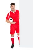 Soccer player pointing at billboard. Full length portrait of young soccer player with football pointing at billboard over white background Royalty Free Stock Photo