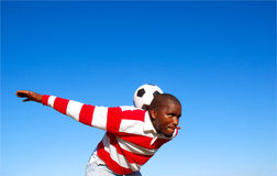 Soccer player practising with ball. Outdoor portrait of an African American black football player in a red and white jersey practising to keep the soccer ball in Royalty Free Stock Images