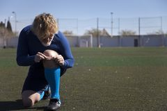 Soccer player puts a band aid on his knee royalty free stock photos