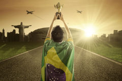 Soccer player raising a trophy at road Royalty Free Stock Image