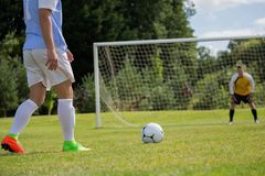 Soccer player is ready to kick ball from penalty spot. In the ground Stock Photos