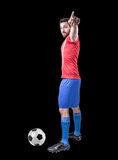 Soccer player on red and blue uniform on black background Stock Photos