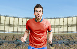 Soccer player on red and blue uniform in the stadium Royalty Free Stock Images