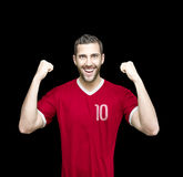 Soccer player on red uniform on black background Stock Images