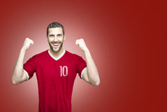 Soccer player on red uniform on red background Royalty Free Stock Photos