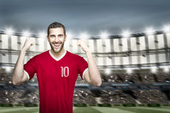 Soccer player on red uniform in the stadium Stock Photography
