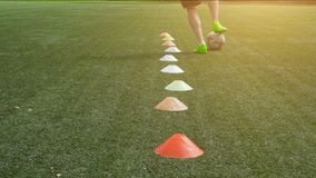 Soccer player running in football field leading ball between cones. Leg skill training on football field. Low angle view of young soccer player running in stock video footage