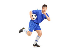 A soccer player running and gesturing silence. On white background Royalty Free Stock Photography