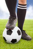 Soccer player's feet and football. With sky background stock images