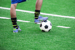 Soccer player's feet stepping onto a soccer ball Stock Image
