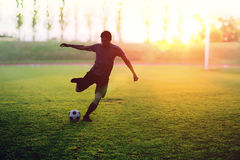 Soccer player is shooting a ball in stadium at sunset Royalty Free Stock Photo