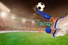 Soccer Player Kicking Football in Outdoor Stadium With Copy Spac. Soccer player with spectacular scissor kick of football in brightly lit outdoor stadium. Focus stock photo